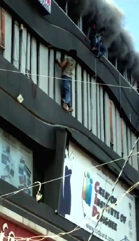 Surat: Students try to escape the massive fire that broke out at a coaching centre atop a four-storey building, by jumping off the building in panic, in Sarthana area of Gujarat's Surat on May 24, 2019. 17 students were killed in the incident. (Photo