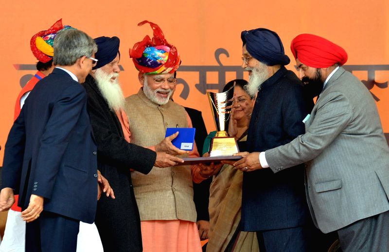 Prime Minister Narendra Modi at the launch of the `Soil Health Card scheme`, at Suratgarh, in Rajasthan on Feb 19, 2015. Also seen Chief Minister of Rajasthan Vasundhara Raje Scindia, ... - Narendra Modi and Parkash Singh Badal
