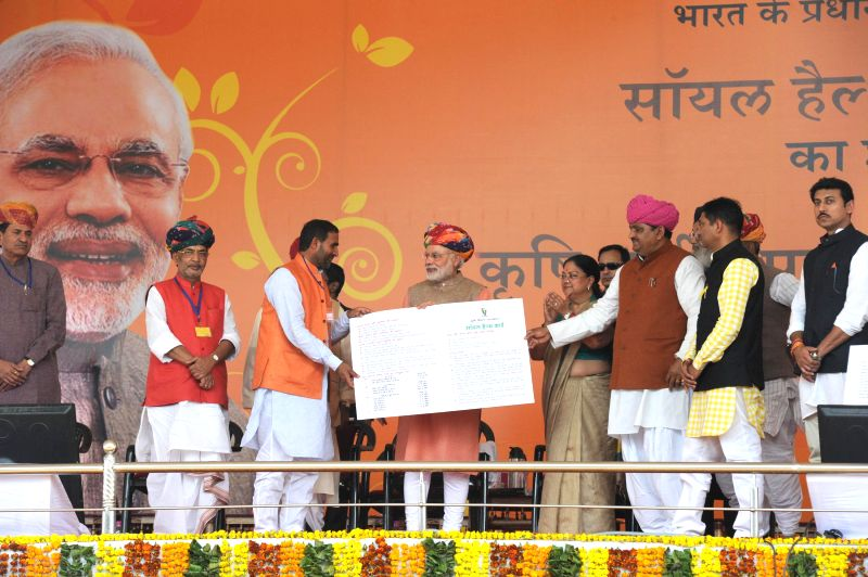 Prime Minister Narendra Modi presents `Soil Health Card` to a farmer at the launch of the `Soil Health Card scheme`, at Suratgarh, in Rajasthan on Feb 19, 2015. Also seen the Union ... - Narendra Modi and Radha Mohan Singh