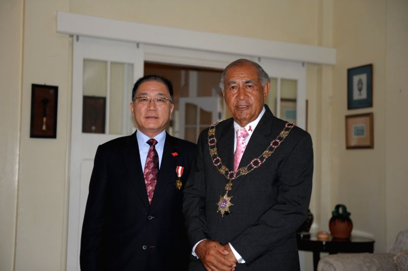 Fijian President Ratu Epeli Nailatikau (R) takes group photos with outgoing Chinese Ambassador to Fiji Huang Yong after awarding him the Honorary Officer of the Order .