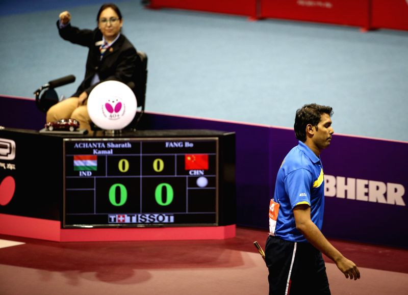 India's Sharath Kamal Achanta(R) quits after his first shot during his Men's Singles match against China's Fang Bo at the 53rd Table Tennis World Championships in ...
