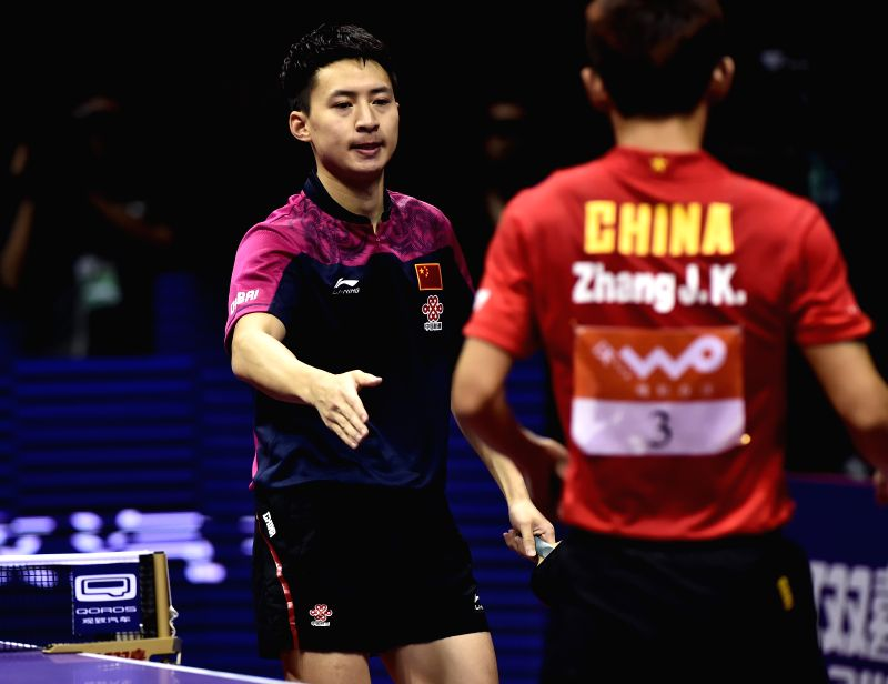 China's Fang Bo(L) shakes hands with his compatriot Zhang Jike after winning Men's Singles Semifinal at the 53rd Table Tennis World Championships in Suzhou, city of ...
