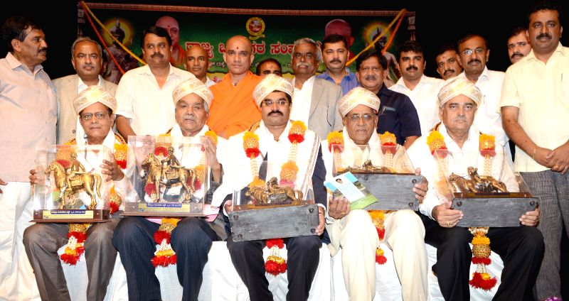 Swami Nirmalananda with members of Karnataka Vokkaliga Association during 'Kempegowda Jayantotsava' organized by the association  at Kuvempu Kalakshetra in Bangalore on April 27, 2014.
