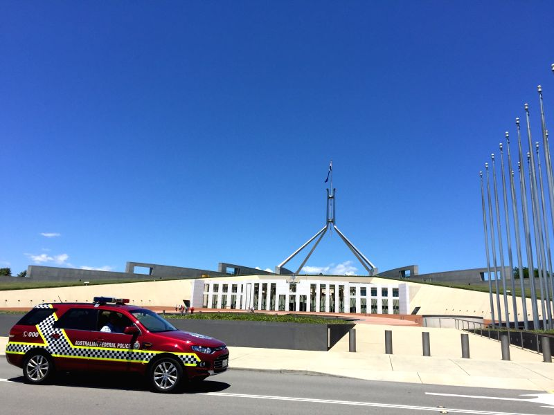A police patrol car passes the forecourt of the Parliament House hours after a few gunmen took people hostage in a cafe in Sydney CBD, in Canberra, Australia, Dec. ..