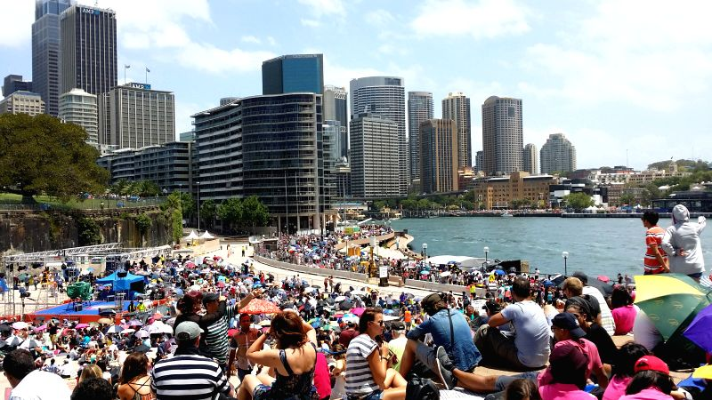 Thousands of people gather near the Opera House in Sydney as they wait for a harbourside vantage point to open to the public for New Year's Eve fireworks Dec. 31, ...