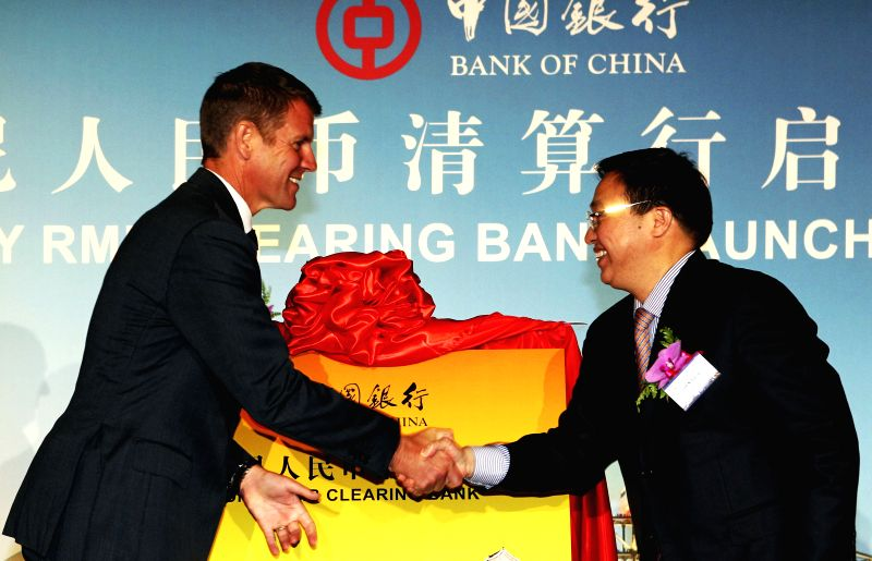 Bank of China President Chen Siqing (R) and Australia's New South Wales state Premier Mike Baird shake hands at the launching ceremony of Bank of China's Sydney RMB ..
