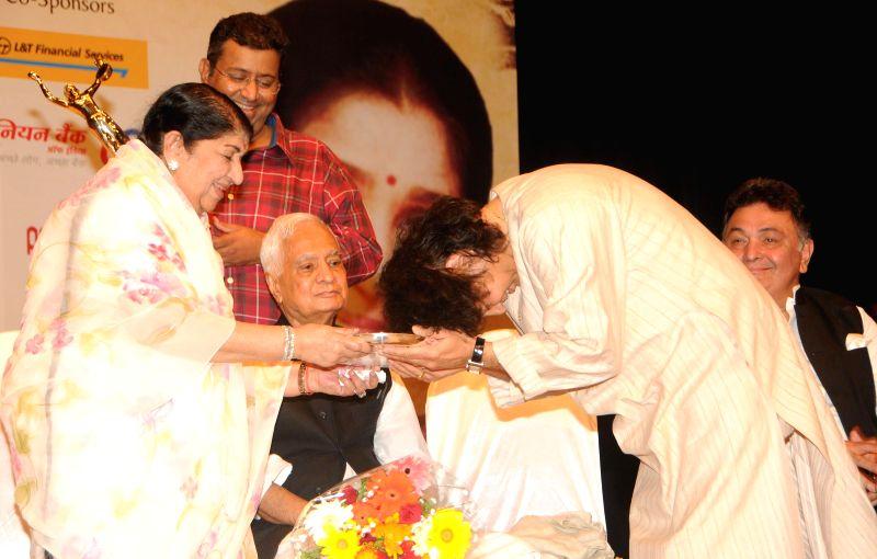 Tabla player Ustad Zakir Hussain receives 25th Master Dinanath Mangeshkar Puraskar from Bollywood singer Lata Mangeshkar in Mumbai on April 24, 2014.