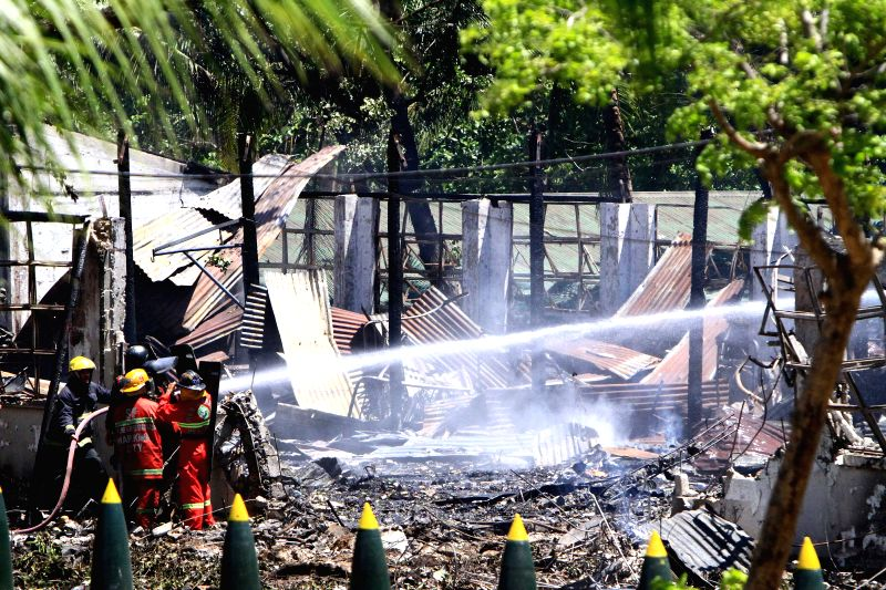 Firefighters try to put out a fire after a powerful explosion that rocked the Philippine Army's Explosives and Ordnance Division (EOD) building inside Fort ...