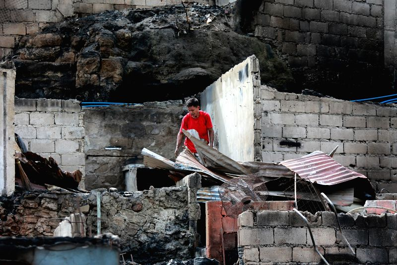 TAGUIG CITY, Nov. 30, 2017 - A resident returns to his burnt home to retrieve usable wares after a fire at a slum area in Taguig City, the Philippines, Nov. 30, 2017. More than 200 families were left ...