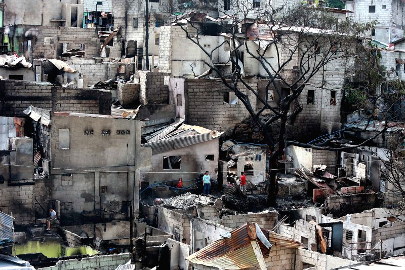 TAGUIG CITY, Nov. 30, 2017 - Residents return to their burnt home to retrieve usable wares after a fire at a slum area in Taguig City, the Philippines, Nov. 30, 2017. More than 200 families were left ...