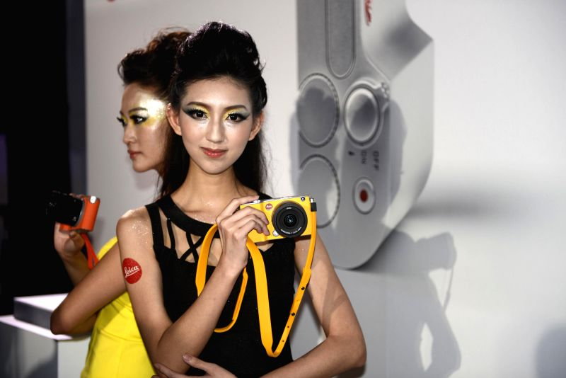 Models demonstrate the brand-new Leica T cameras at a release ceremony in Taipei, southeast China's Taiwan, April 30, 2014. German camera manufacturer Leica ...