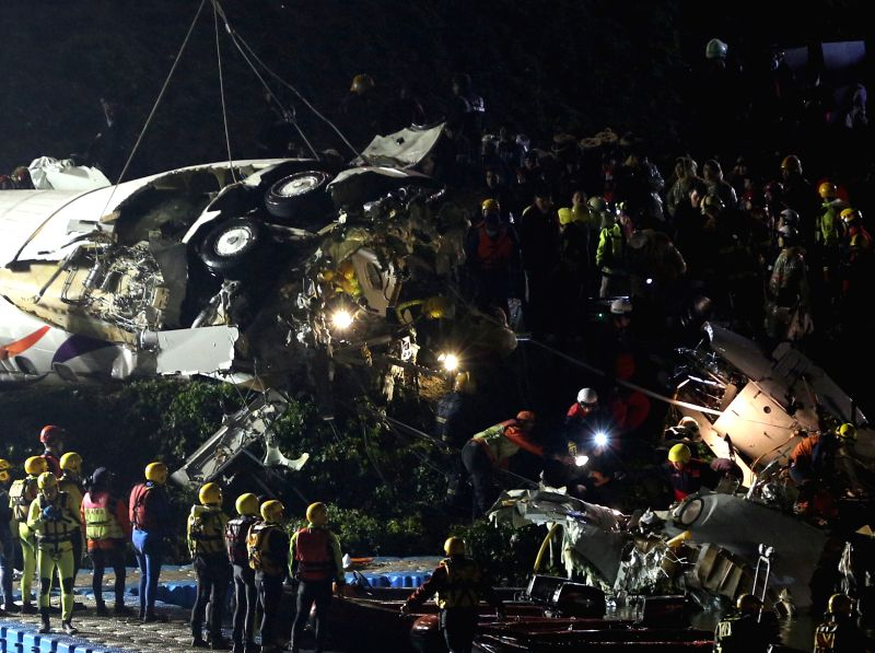 Rescuers work on the plane wreckage salvaged from the Keelung River in Taipei, southeast China's Taiwan, Feb. 4, 2015. By 10 p.m. on Wednesday, at least 25 people ...