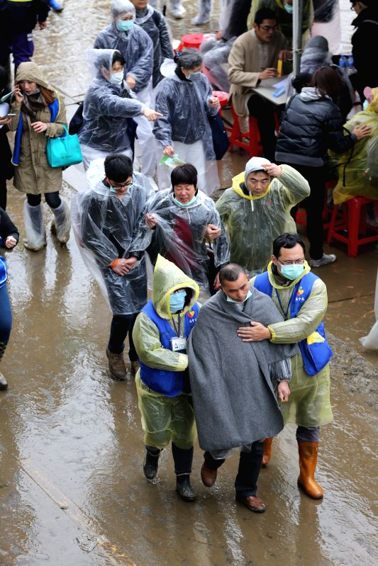 Relatives of victims and missing passengers of a plane crash leave the rescue site in Taipei, southeast China's Taiwan, Feb. 6, 2015. Rescuers expanded the search ...