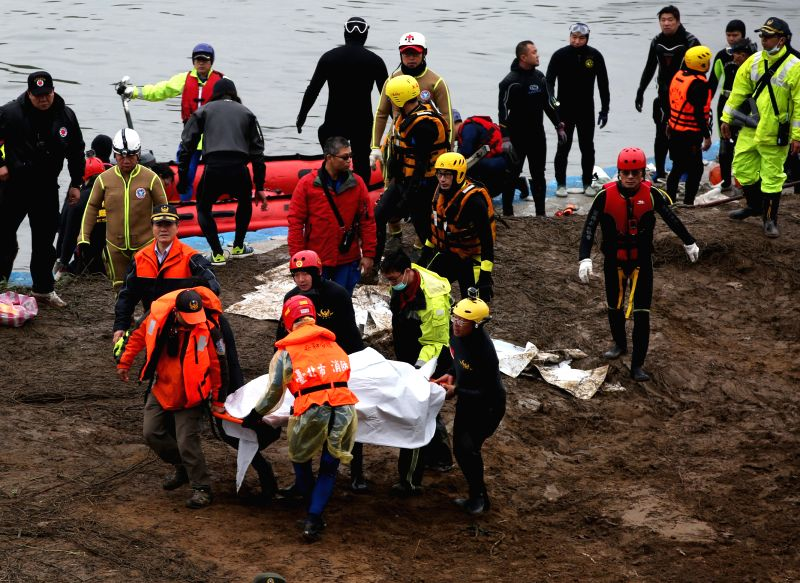 Rescuers transfer the body of a plane crash victim on the bank of the Keelung River in Taipei, southeast China's Taiwan, Feb. 6, 2015. Rescuers expanded the search ...