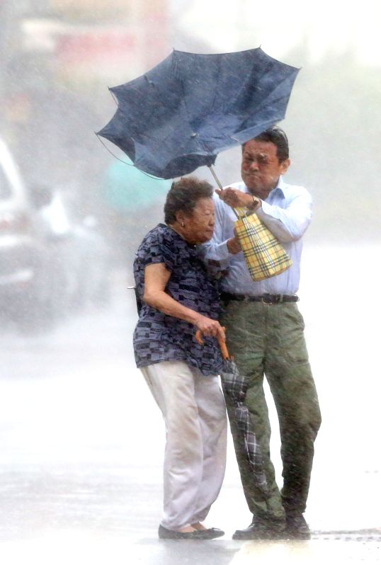 A man's umbrella is turned over by the strong wind in Taipei, southeast China's Taiwan, July 23, 2014. Typhoon Matmo, the 10th typhoon affecting China this year, hit