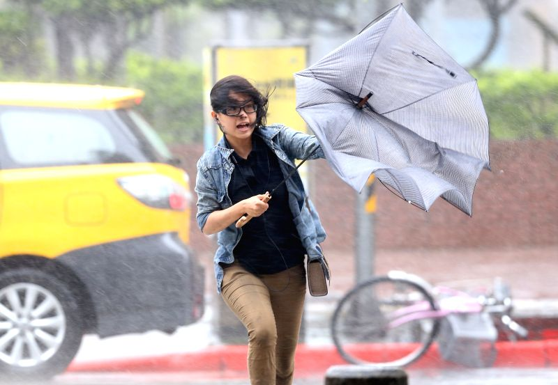 A woman's umbrella is turned over by the strong wind in Taipei, southeast China's Taiwan, July 23, 2014. Typhoon Matmo, the 10th typhoon affecting China this year, ..