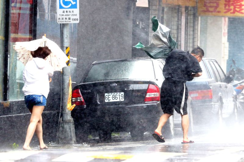 People's umbrellas are turned over by the strong wind in Taipei, southeast China's Taiwan, July 23, 2014. Typhoon Matmo, the 10th typhoon affecting China this year, .