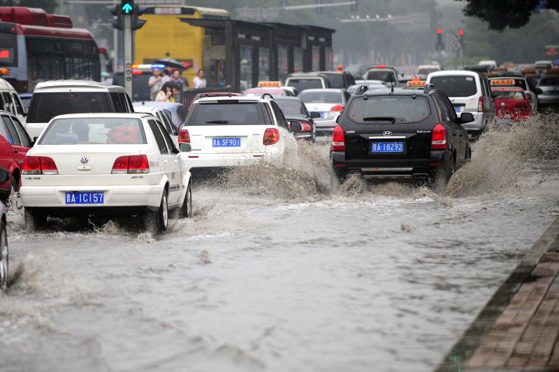 Cars drive on a waterlogged road in Taiyuan, capital of north China's Shanxi Province, Aug. 4, 2014. Heavy rainfall hit the city on Monday.  ..