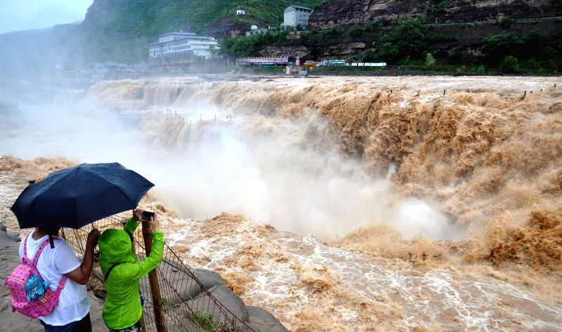 Tourists take photos of the Hukou Waterfall of the Yellow River, north China's Shanxi Province, July 9, 2014.