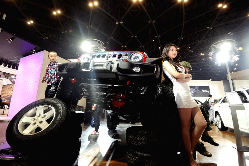 A model presents a Jeep Wrangler during the 2014 China (Taiyuan) International Automobile Exhibition in Taiyuan, capital of north China's Shanxi Province, May 15, ...