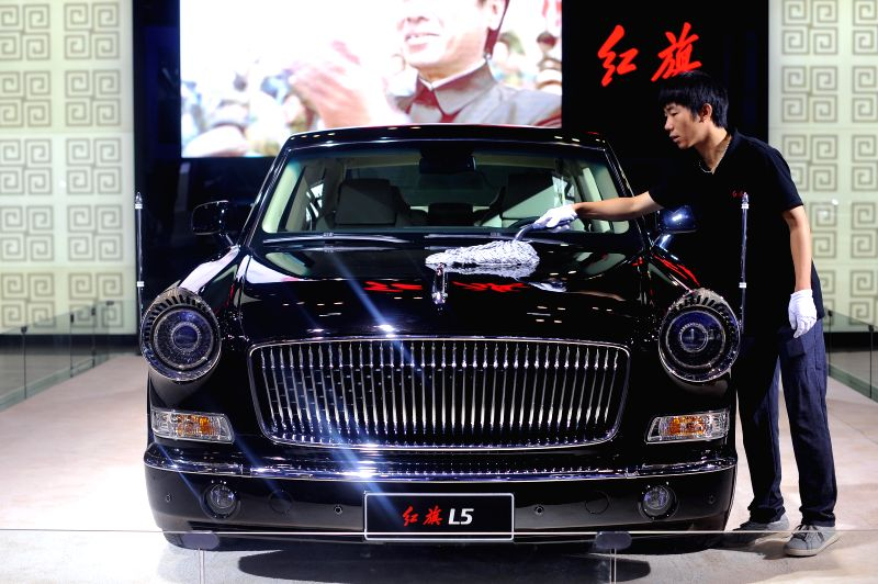 An exhibitor cleans a Hongqi L5 during the 2014 China (Taiyuan) International Automobile Exhibition in Taiyuan, capital of north China's Shanxi Province, May 15, ...