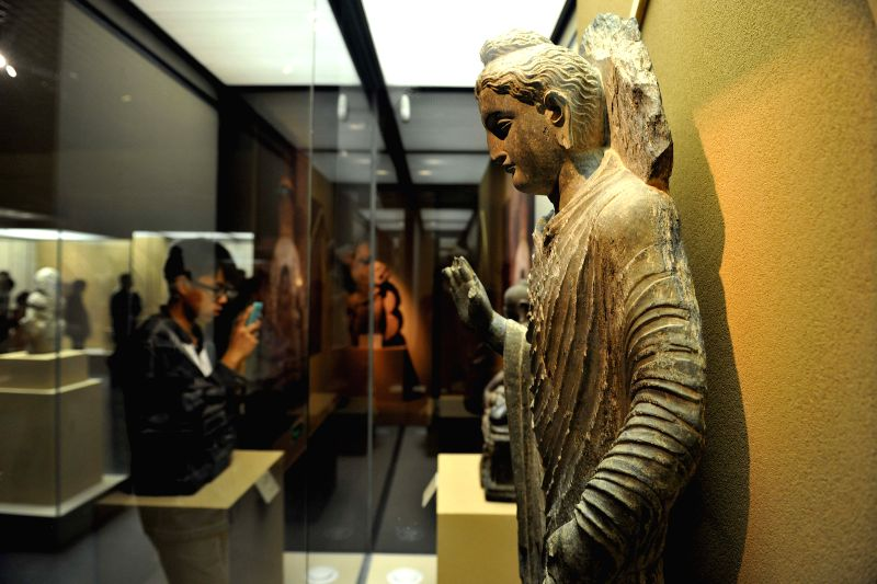 "A visitor takes photos of a stone sculpture at ""India's Universe"", an exhibition of Indian cultural masterworks from the Los Angeles County Museum of Art ..."