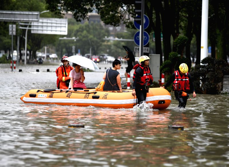 TAIZHOU, Aug. 10, 2019 (Xinhua) -- Rescuers transfer the flood-stranded people in Wenling, east China's Zhejiang Province, Aug. 10, 2019. Typhoon Lekima, the ninth of the year, made landfall on Saturday in Wenling City. Rescue and clean-up works were