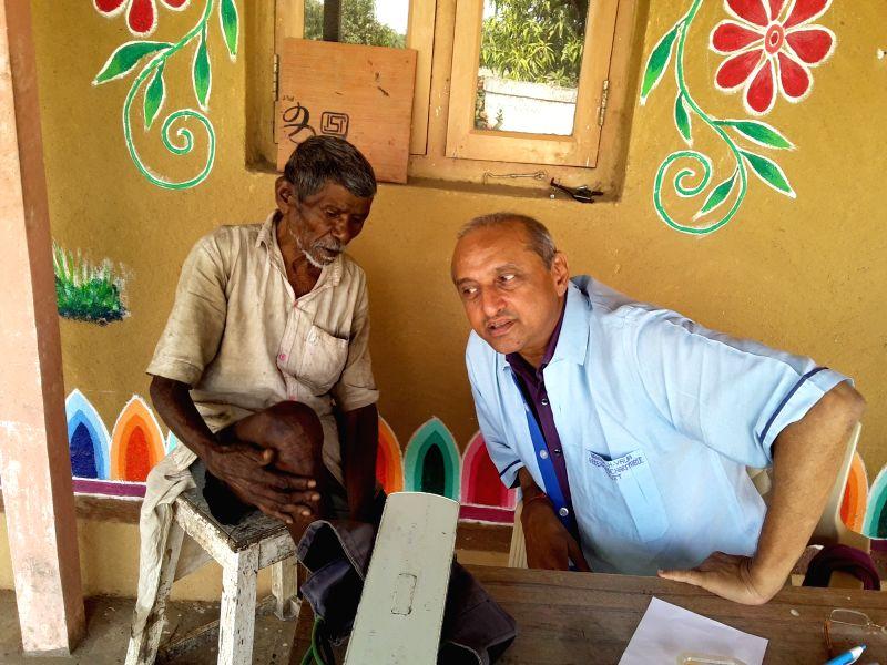 Talasari: Mumbai Homoeopathic doctor Jatin N. Valia during the treatment of a patient at a medical camp in Talasari. (Photo: IANS)