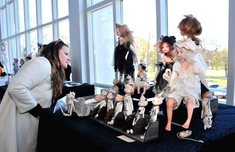 Photo taken on May 2, 2014 shows a visitor watching exhibit dolls on the Internatinal Charity Doll Exhibition in Tallinn, capital city of Estonia. The exhibition ...