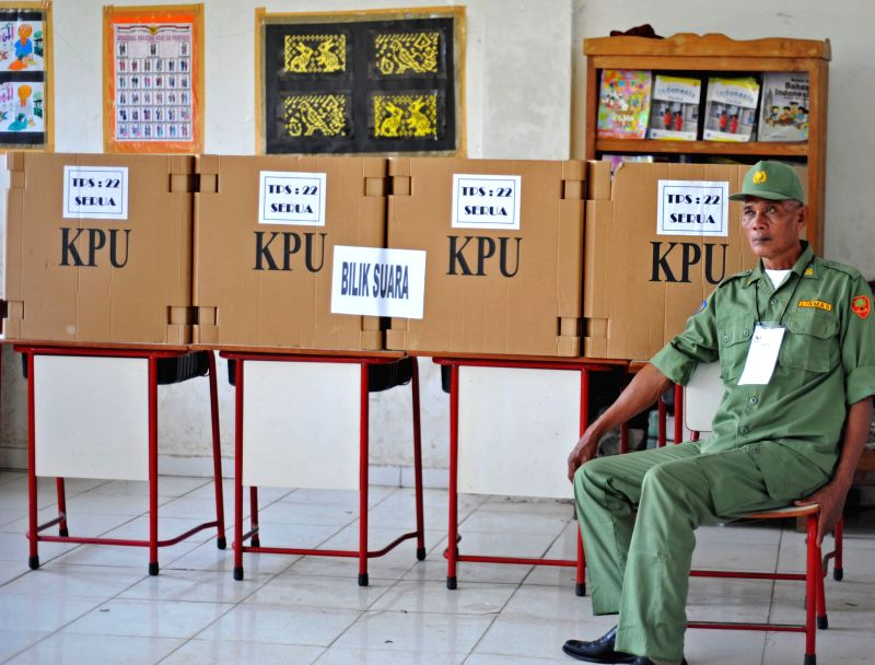 A security official waits for voters at a polling station in Tangerang, Indonesia, July 9, 2014. Indonesians on Wednesday went to polls to pick up their new ...