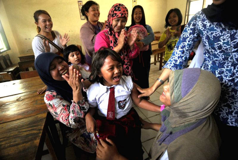 An elementary schoolgirl laughs during the school children immunization month held by paramedics in Tangerang, Indonesia, Sept. 4, 2014. School children ...