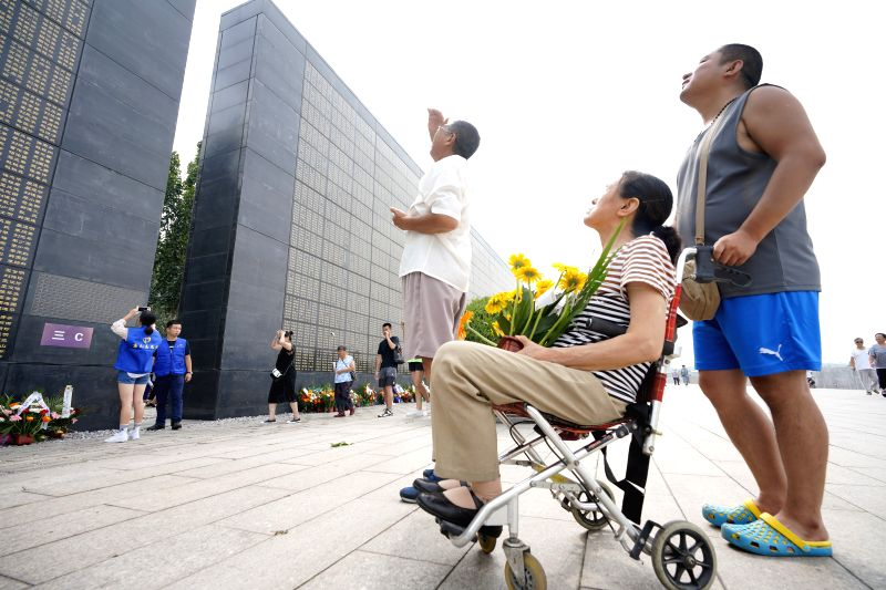 TANGSHAN, July 27, 2018 - People search for the names of their relatives killed in the 1976 Tangshan earthquake in front of the memorial wall in Tangshan, north China's Hebei Province, July 27, 2018, ...
