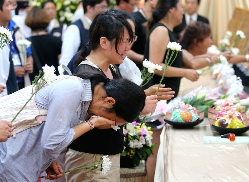 TAOYUAN, July 21, 2016 - Families mourn in front of victims' portraits at Zhongli funeral home in Taoyuan, southeast China's Taiwan, July 21, 2016. Families of mainland victims of a deadly tour-bus ...