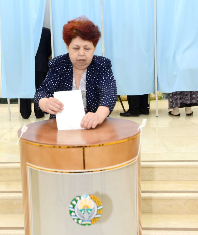A woman casts her ballot at No. 76  polling station in Tashkent, capital of Uzbekistan, on March 29, 2015. Voting for presidential election of Uzbekistan began ...