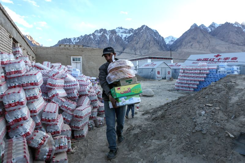 TAXKORGAN, May 12, 2017 - A villager carries quake-relief materials at an emergency shelter in Quzgun Village of quake-hit Taxkorgan County, northwest China's Xinjiang Uygur Autonomous Region, May ...