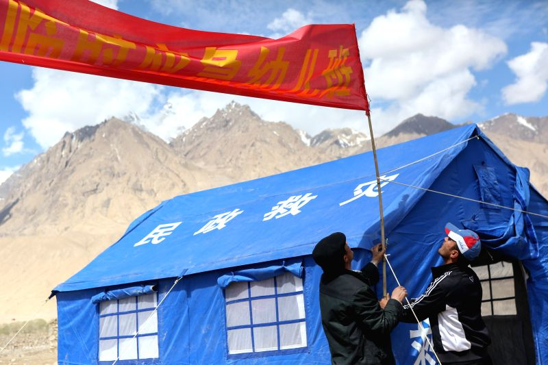 TAXKORGAN, May 13, 2017 - Rescuers set up a banner for a temporary kindergarten of an emergency shelter in Quzgun Village of quake-hit Taxkorgan County, northwest China's Xinjiang Uygur Autonomous ...