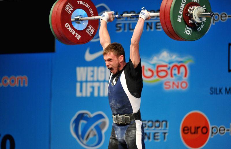 Oleg Sirghi of Moldova competes during the men's 56kg final of the European Weightlifting Championship in Tbilisi, Georgia, April 11, 2015. (Xinhua/Kulumbegashvili ...