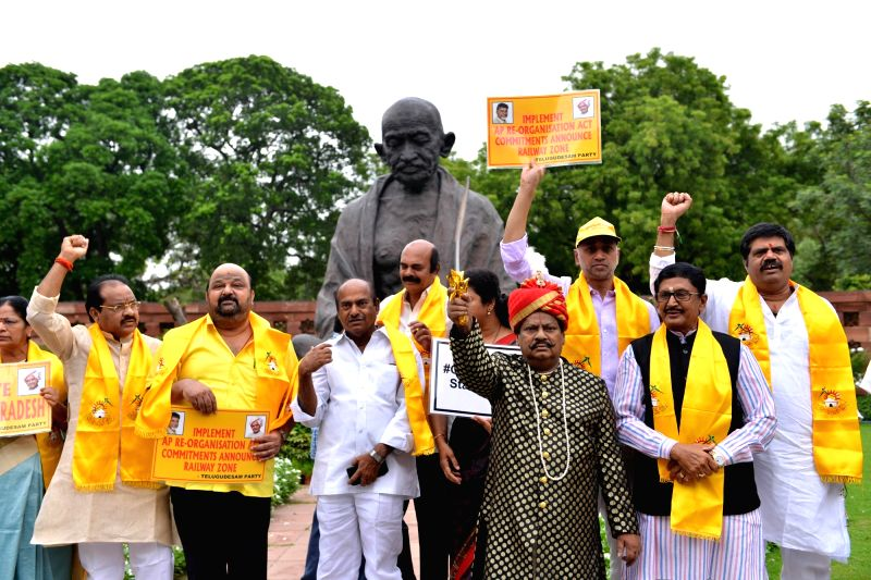 TDP MPs led by Chittoor Naramalli Sivaprasad stage a demonstration demanding special category status for Andhra Pradesh; in front of Gandhi statue at Parliament in New Delhi on July 25, ...