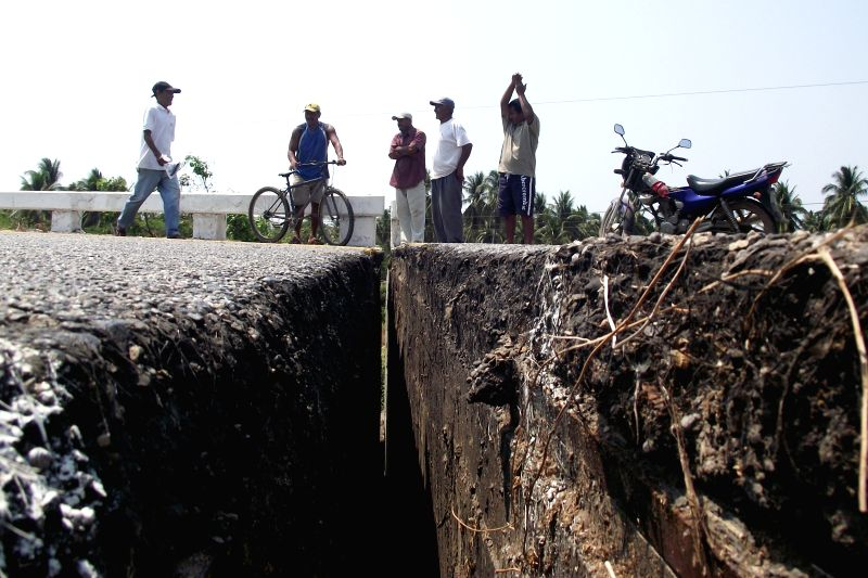 Mexicans inspect a crack on the federal road Acapulco-Zihuatanejo, after an earthquake, in Tecpan, Guerrero, Mexico, on April 18, 2014. According to China ...