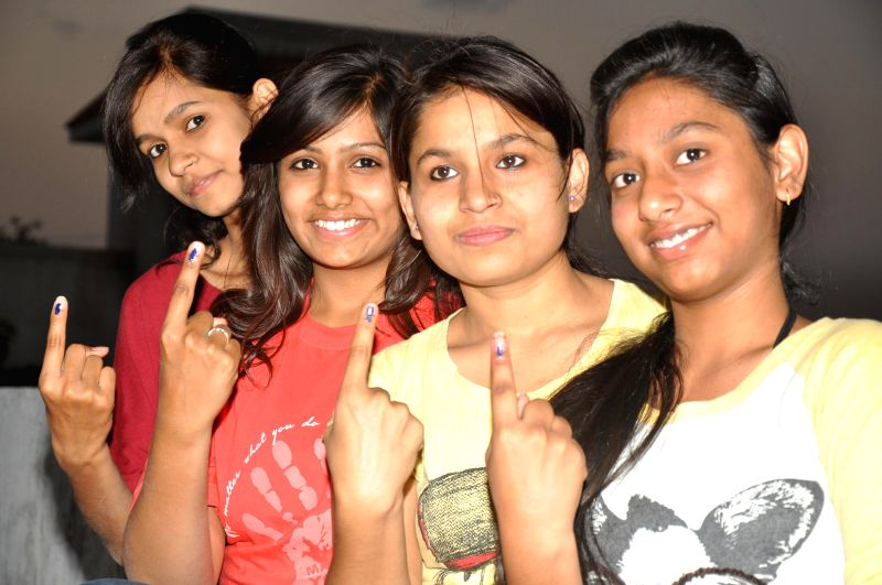 Teenagers show their fore fingers marked with phosphoric ink after casting their votes during the third phase of 2014 Lok Sabha Polls in Jabalpur on April 10, 2014. Elections are being held in 91 ...
