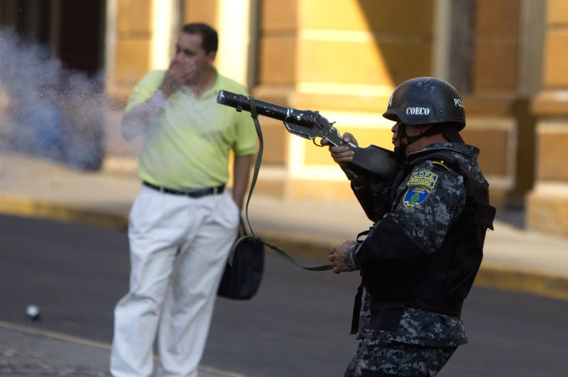 A police element participates in a clash against followers of the former Honduran President Manuel Zelaya in front of the National Congress, in Tegucigalpa, ...