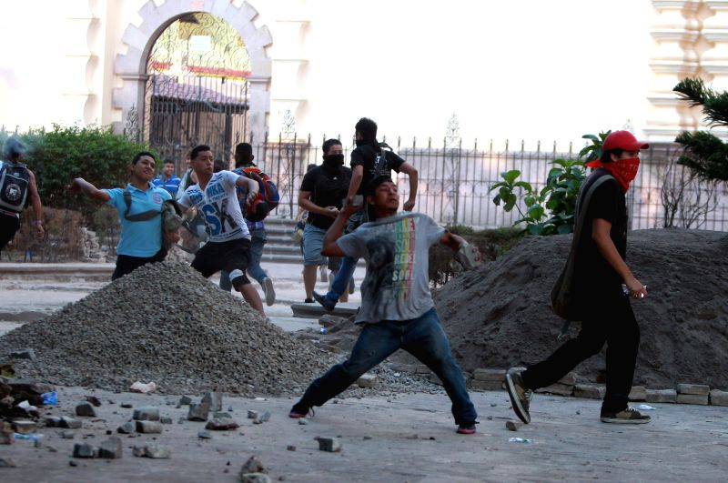 Supporters of the former Honduran President Manuel Zelaya clash with police in front of the National Congress in Tegucigalpa, Honduras, on May 13, 2014. ...