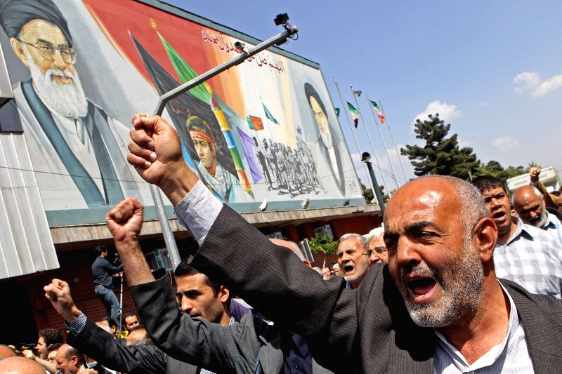 Iranian protesters shout slogans during a demonstration after Friday prayers in downtown Tehran, Iran, on April 11, 2014. Iranian protesters attended a protest in ..
