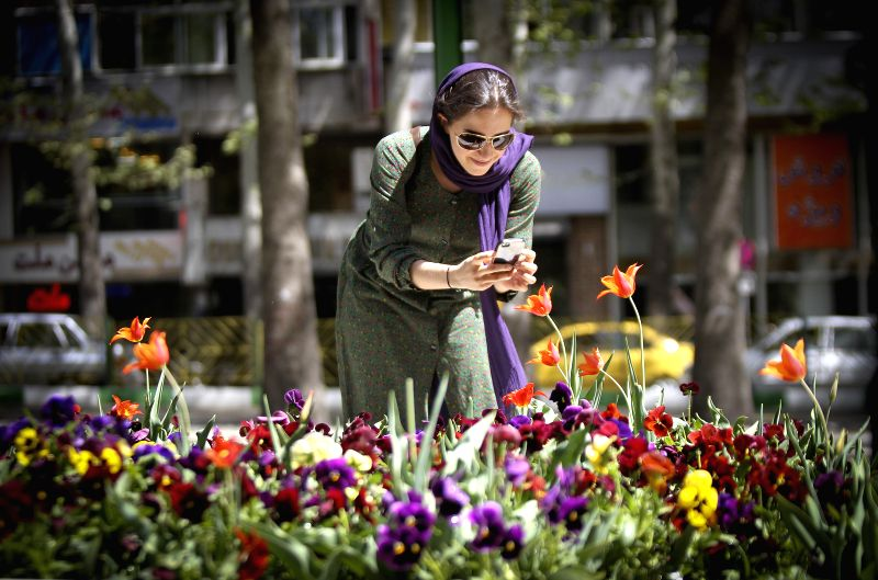 A woman takes pictures of flowers at a park in northern Tehran, Iran, on April 16, 2014. Spring flowers blossom here as temperature rises.