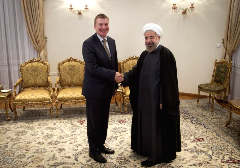 Iranian President Hassan Rouhani shakes hands with Latvian Foreign Minister Edgars Rinkevics at the Presidential Palace in Tehran, Iran, on April 23, 2014.