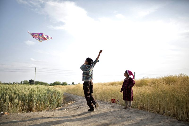 TEHRAN, April 27, 2017 - File photo taken on May 12, 2016 shows a Pakistani refugee boy flying a kite as another child looks on, on the outskirts of Tehran, capital of Iran. Located in West Asia, ...