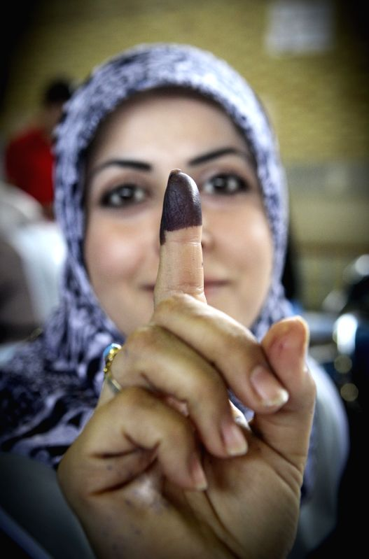 An Iraqi woman living in Iran shows her inked finger after casting her vote at an overseas polling station for Iraq's parliamentary elections in southern Tehran, ...