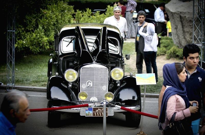 Visitors watch a car displayed during a classic car exhibition in Tehran, Iran, on Aug. 8, 2014. More than 70 classic cars are displayed during the six-day-long ...
