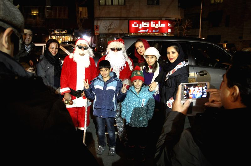 Members of an Iranian family pose for photos beside two men dressed as Santa Claus on a street in Tehran, Iran, on Dec. 24, 2014. Iran has more than 200,000 ...