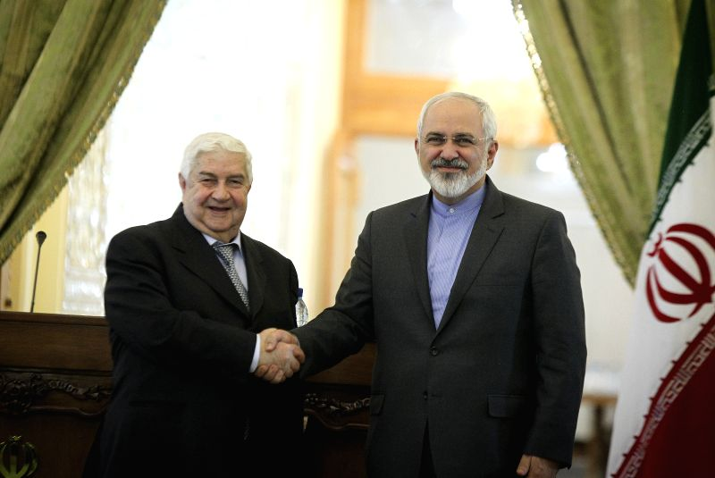 Iranian Foreign Minister Mohammad-Javad Zarif (R) shakes hands with his Syrian counterpart Walid al-Moallem during a joint press conference in Tehran, Iran, on Dec. 8, 2014. Iran seeks a ... - Mohammad-Javad Zarif